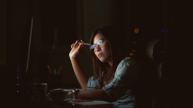 4k footage scene of attractive asian woman working late and thinking with serious action on the table in front of computer monitor desktop at workplace in the dark, work late and work hard concept - lighting technique stock videos & royalty-free footage