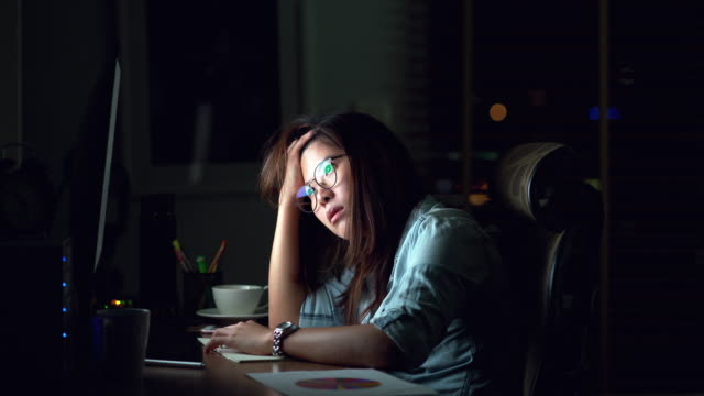 4k footage scene of Attractive Asian woman working late and thinking with serious action on the table in front of computer monitor desktop at workplace in the dark, Work late and Work hard concept