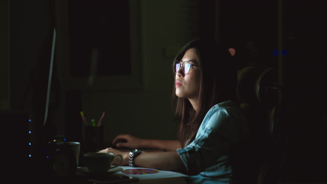 4k footage scene of Attractive Asian woman working late with serious action on the table in front of computer monitor desktop at workplace in the dark, Work late and Work hard concept