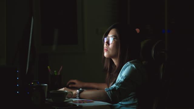 vídeos de stock, filmes e b-roll de cena de filmagem 4 k de atraente mulher asiática trabalhando até tarde com ação séria na mesa na frente do computador desktop monitor no local de trabalho no escuro, trabalhar até tarde e trabalhar duro conceito - excesso de trabalho