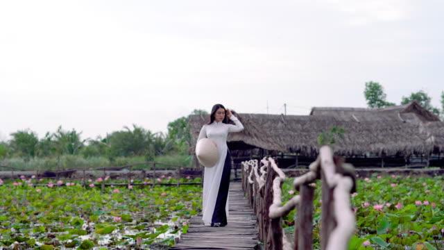vídeos y material grabado en eventos de stock de escena de secuencias de 4 k de hermosa mujer vietnamita caminando y obtener aire fresco en el puente de madera en concepto de viajes de asia o asia sudoriental de lotus grande lago, vietnam, - posa del loto