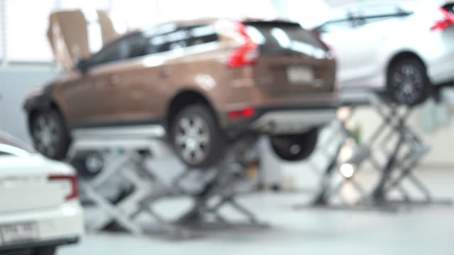 4k footage scene of blurred background of car lifted in automobile service, transportation and maintenance car concept - lug wrench stock videos and b-roll footage
