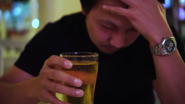 4k footage scene of Broken Hearted Asian man drinking a glasses of beer with sadness and upset at pub bar and restaurant, relax and drink concept