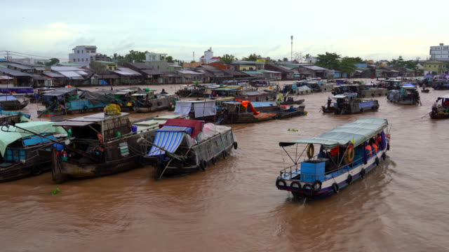 4k footage scene of cargo ships in traditional market at port of cai rang floating market, can tho province, mekong delta, vietnam, transportation and merchandise concept - floating on water stock videos & royalty-free footage