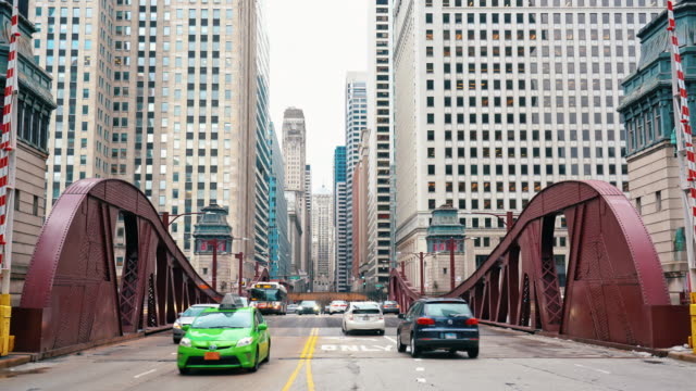 4k footage scene of chicago street bridge with traffic among modern buildings of downtown chicago at michigan avenue in chicago, illinois, united states - michigan avenue bridge stock videos and b-roll footage