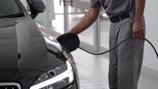 vídeos de stock e filmes b-roll de 4k footage scene of closeup hand of man plugging in hybrid electric vehicles for charging battery ev car, transportation and car service concept - power line