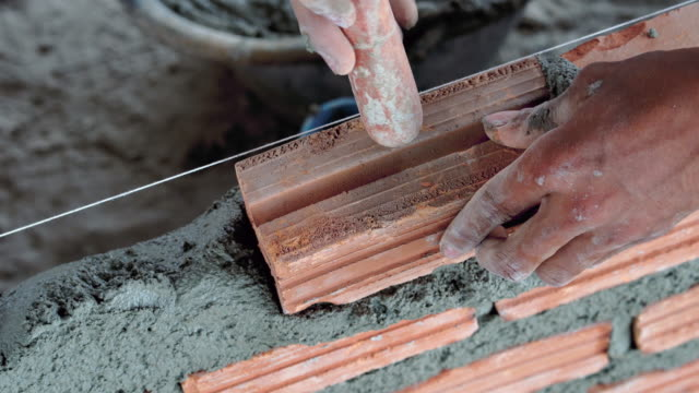 4k footage scene of closeup hand professional construction worker laying bricks in new industrial site, construct industry and masonry concept - brick stock videos & royalty-free footage