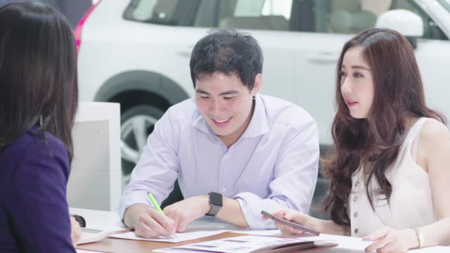 販売のための契約を署名し、カップルの顧客の4k 映像シーン - 自動車ショールーム点の映像素材/bロール
