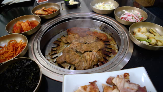 4k footage scene of grilling Pork on charcoal grill pan with side dishes traditional Korean food, Korean style and barbecue concept