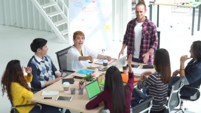 4 k Filmmaterial Szene der Gruppe der asiatischen und multiethnischen Business Menschen mit lässigen Anzug Brainstorming und Austausch von neuen Ideen mit glücklich Aktion in der modernen Arbeitswelt Menschen Gruppe Geschäftskonzept