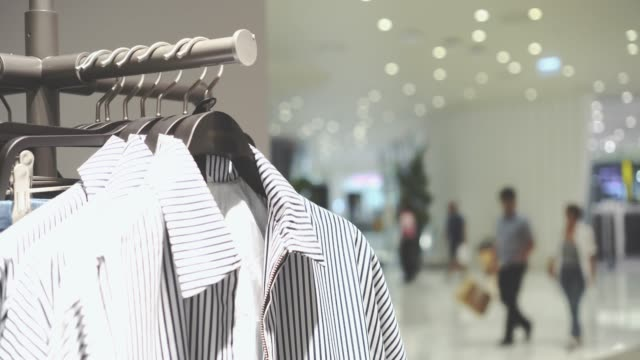 4k footage scene of hanging clothes rack and rail on clothes hangers and people shopping in fashion clothes shop at department store, shopping mall and clothing concept - label stock videos & royalty-free footage