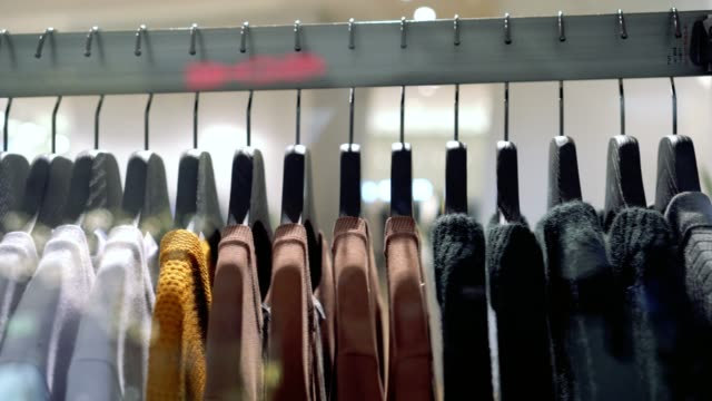 4k footage scene of hanging clothes rack and rail on clothes hangers in fashion clothes shop at department store, shopping mall and clothing concept - fare spese video stock e b–roll