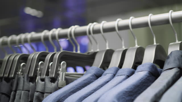 4k footage scene of hanging clothes rack and rail on clothes hangers in fashion clothes shop at department store, shopping mall and clothing concept - department store stock videos and b-roll footage