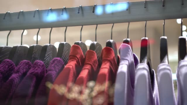 4k footage scene of hanging clothes rack and rail on clothes hangers in fashion clothes shop at department store, shopping mall and clothing concept - rack stock videos & royalty-free footage