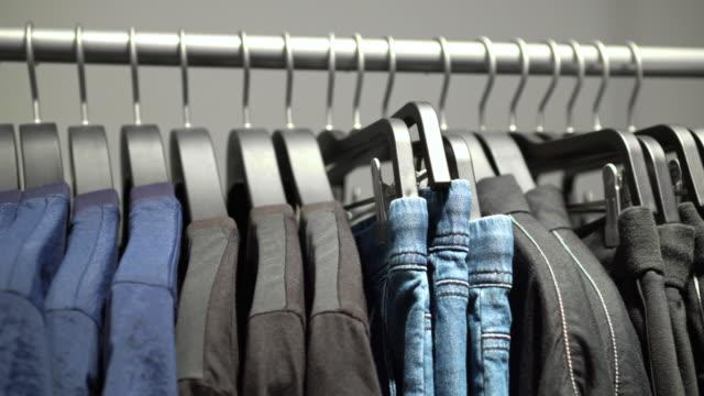 vidéos et rushes de scène d'images de 4k de support et de rail suspendus de vêtements sur des cintres de vêtements dans le magasin de vêtements de mode au grand magasin, au centre commercial et au concept de vêtement - entrepôt