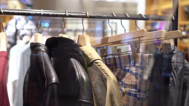 デパート、ショッピングモール、衣料品コンセプトのファッション衣料品店で衣類ハンガーに衣類ラックやレールを吊るす4k映像シーン - オーバーコート点の映像素材/bロール