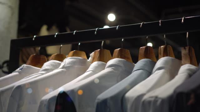 4k footage szene von hängenden kleiderständer und schiene auf kleiderbügel in mode-kleidungsgeschäft im kaufhaus, einkaufszentrum und kleidung konzept - wahlmöglichkeit stock-videos und b-roll-filmmaterial