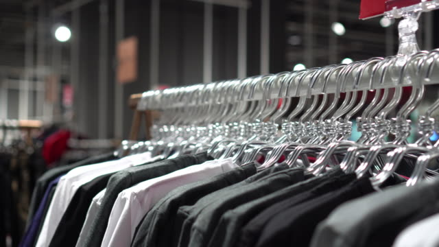 4k footage scene of hanging clothes rack and rail on clothes hangers in fashion clothes shop at department store, shopping mall and clothing concept - coathanger stock videos & royalty-free footage