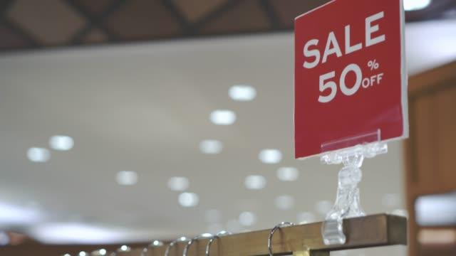 vídeos de stock, filmes e b-roll de cena de filmagem 4 k de pendurar cabideiro e trilho com display de venda em cabides de roupas em loja de roupas da moda na loja de departamentos, shopping e conceito de vestuário - estação do ano