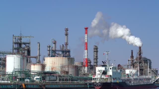 蒸気煙、工場、産業と汚染の概念を持つ川の横の石油精製所工業地帯の4k映像シーン - 発電所点の映像素材/bロール