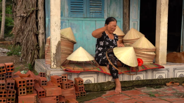 4k footage scene of old vietnamese craftsman making the traditional vietnam hat in the old traditional house in ap thoi phuoc village, cantho province, vietnam, traditional artist concept - traditionally vietnamese stock videos & royalty-free footage