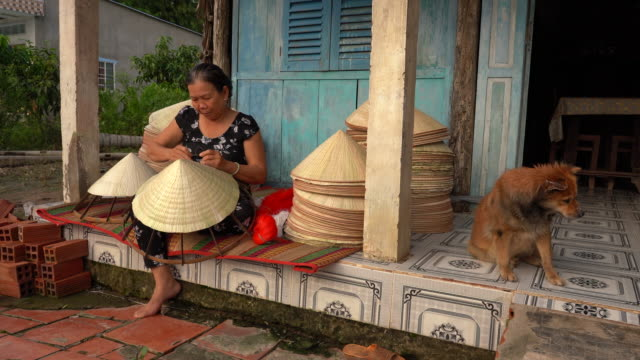 4k footage scene of old vietnamese craftsman making the traditional vietnam hat in the old traditional house in ap thoi phuoc village, cantho province, vietnam, traditional artist concept - vietnam stock videos & royalty-free footage