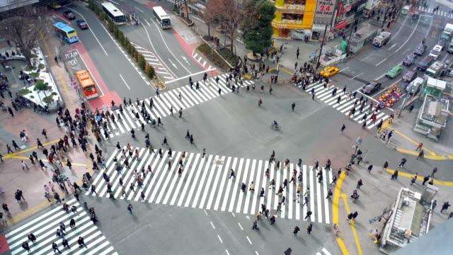 ●歩行者・車群集の4k 映像シーンは未定義の人たちが道路の交差点を歩いて、渋谷区東京市にある交差を歩きます。日本文化・商店街構想 - 横断する点の映像素材/bロール