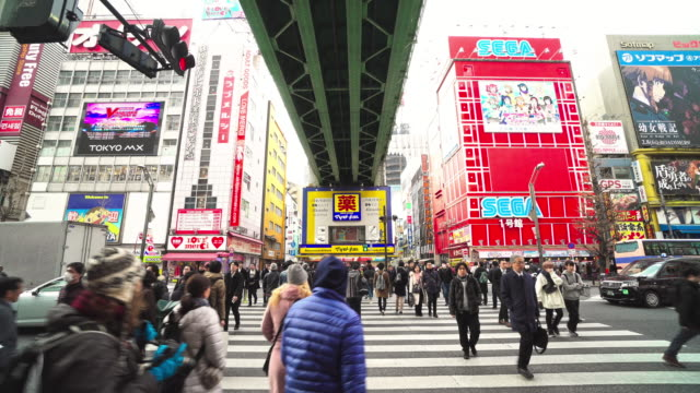4k footage scene of pedestrians crowd undefined people walking overpass the street intersection cross-walk in akihabara tokyo city, japan. japanese culture and electric town shopping area concept - akihabara station stock videos and b-roll footage