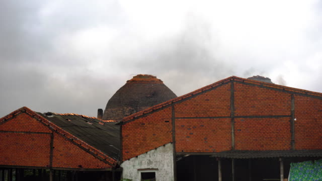 4k footage scene of smoke from kiln riverside at mang thit the land of bricks, vinh long province, vietnam, culture and construction concept - kiln stock videos and b-roll footage