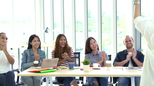 4k footage scene of team leader encourage team member Group of Asian and Multiethnic Business people with casual suit with happy clapping action in the modern workplace, people business group concept