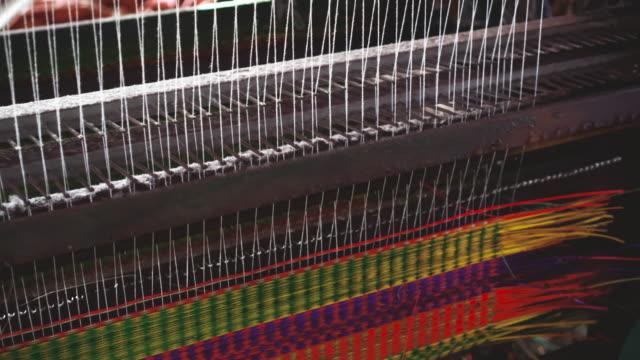 4 k filmmaterial szene des vietnamesischen handwerkerin mit matte webmaschine die traditionelle vietnam-matten im alten traditionellen dorf dinh yen, dong thap, vietnam, tradition und herstellung konzept - teppich stock-videos und b-roll-filmmaterial