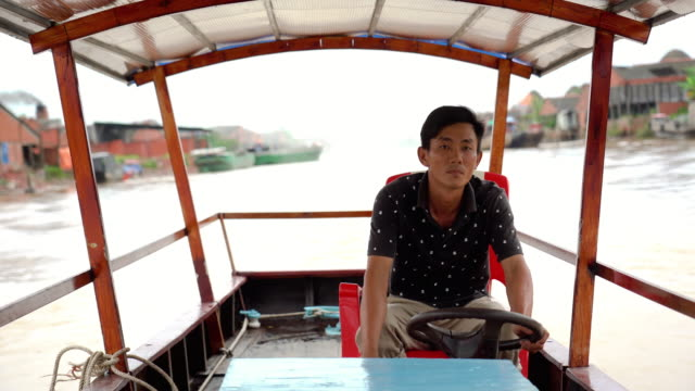 4k footage scene of vietnamese man rowing boat in traditional market at port of cai rang floating market, can tho province, mekong delta, vietnam, transportation and merchandise concept - floating market stock videos & royalty-free footage