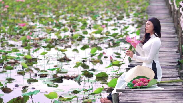 vídeos y material grabado en eventos de stock de escena de imágenes 4k retrato de hermosa mujer vietnamita sosteniendo el loto rosa y sonriendo en el puente de madera en el gran lago de loto, vietnam, asiático o el centro de asia concepto de viaje - posa del loto