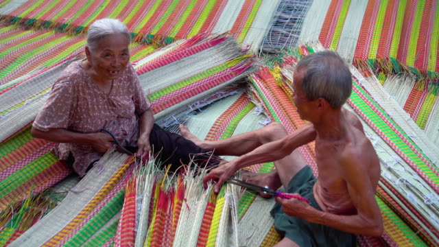 vidéos et rushes de 4 k images scène vue de dessus de deux vietnamiens ancien artisan confection et la finition des tapis vietnam traditionnel dans le vieux village traditionnel à dinh yen, dong thap, vietnam, concept d'artiste de tradition - tisser