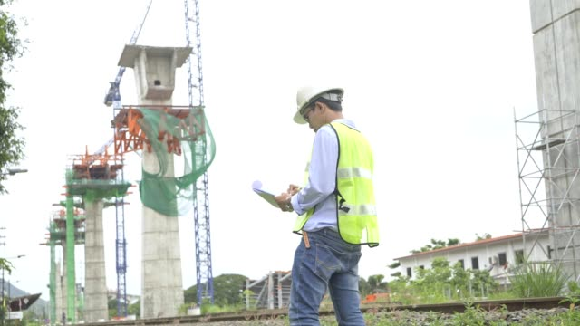 4k footage,asian civil engineer and specialist europe civil engineer talking and discusstion about construction of railway in hand holding clipboard ,tablet,walky talky and wearing safety helmet. - surveyor stock videos & royalty-free footage