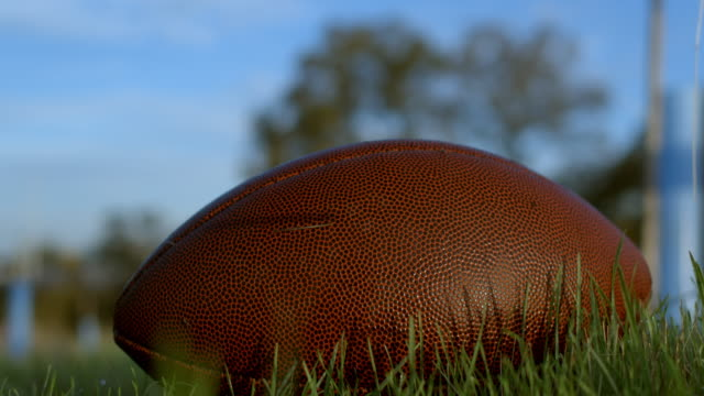 4k football in the grass on a football field. panning across - american football pitch stock videos & royalty-free footage