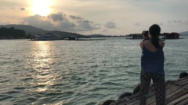4k: girl with camera at raft sunset