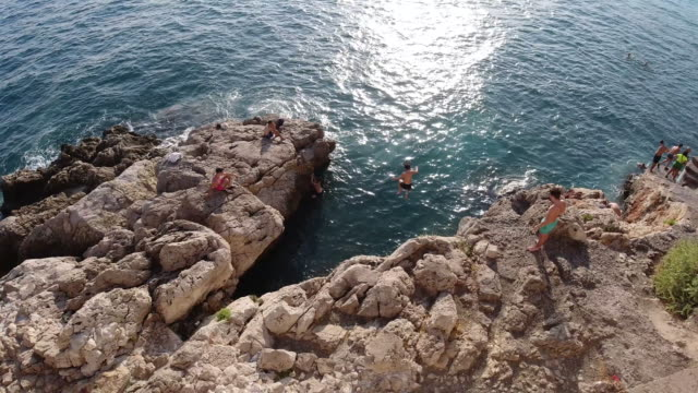 4k group of young men takes turns cliff jumping off the rocks at the beach in nice, france. showing people having fun diving into the sea on a bright summer warm day. - 崖点の映像素材/bロール