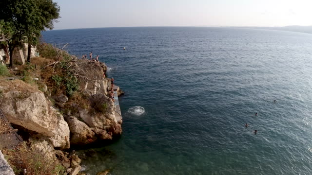 4k group of young men takes turns cliff jumping off the rocks at the beach in nice, france. showing people having fun diving into the sea on a bright summer warm day. - french culture stock-videos und b-roll-filmmaterial