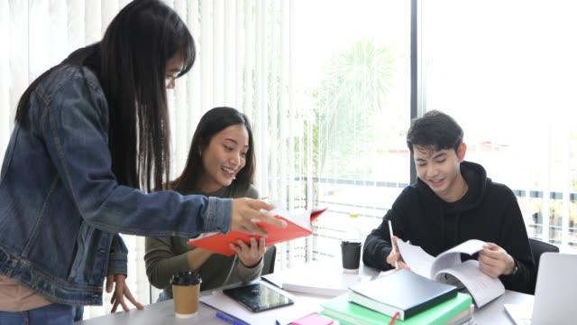 vídeos de stock, filmes e b-roll de 4k grupo estudantes sorriam e divirta-se e usando o tablet também ajuda a compartilhar ideias no trabalho e projeto. e também a ler o livro antes do exame - employee engagement