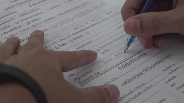vidéos et rushes de 4k: remplissage de formulaire papier à la main - employee engagement