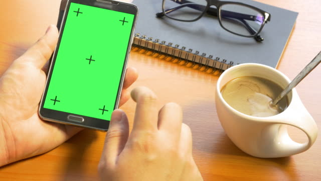 4 k: händchen halten leere handy smartphone auf grünen bildschirm - tischflächen aufnahme stock-videos und b-roll-filmmaterial