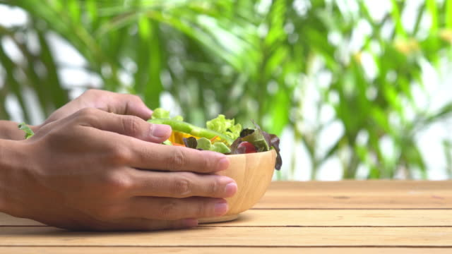 4k holding and lay salad bowl on blur background. - carrying stock videos & royalty-free footage