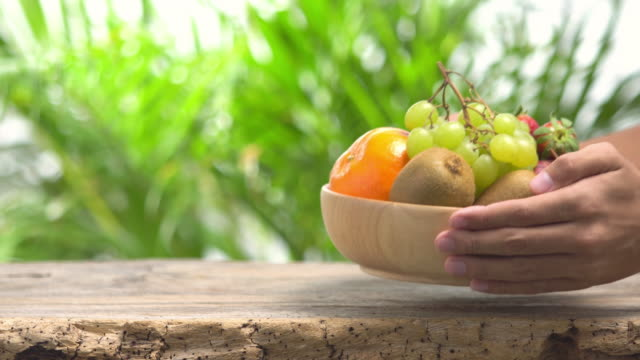 4k human hand lay fruit bowl on leaf background. - fruit bowl stock videos & royalty-free footage