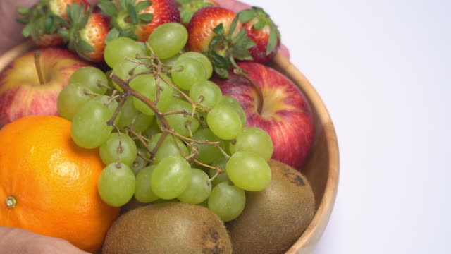 4k human hand lay fruit bowl on white background. - fruit bowl stock videos & royalty-free footage