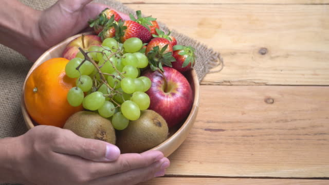 4k human hand lay fruit bowl on wooden background. - fruit bowl stock videos & royalty-free footage