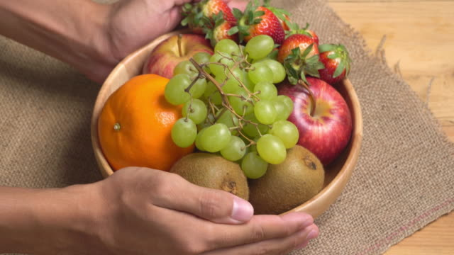4k human hand lay fruit bowl on wooden background. - fruit bowl stock videos and b-roll footage