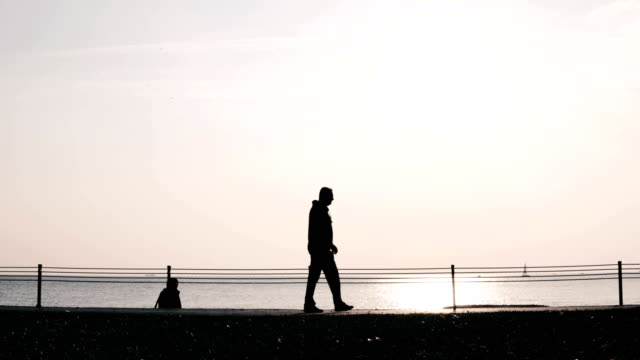 4k human silhouettes walking on the sea shore and cycling - pedestrian stock videos & royalty-free footage