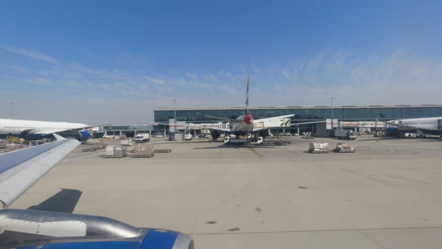 4k hyper lapse from aeroplane window during taxi to runway at london heathrow airport, united kingdom. showing terminal 5 and many other planes taxiing to the runway waiting to take off on a bright summer warm day. - flughafen heathrow stock-videos und b-roll-filmmaterial