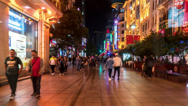 4k hyper lapse: tourist pedestrian crowd walking at nanjing road shopping street at night, shanghai city, china. - nanjing stock videos & royalty-free footage